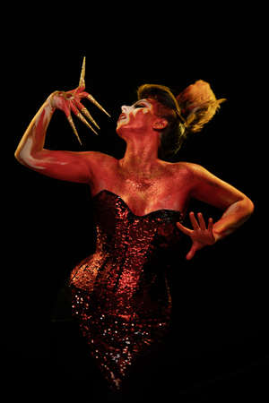 Young woman dancing in the image of Flames and Fire in a red body art emotionally posing on a black background