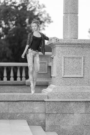 Black and white photo of a ballerina girl in jeans and pointe shoes, dancing and posing in the city on the street Banque d'images