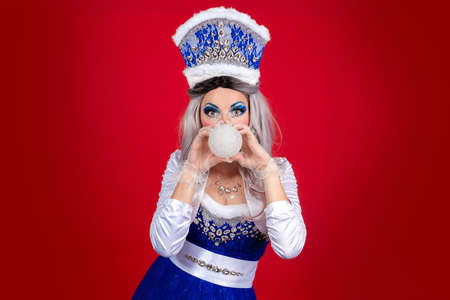 Snow Maiden in an elegant bright blue suit with a crown on her head holds a snow ball in her hands and poses on a red background