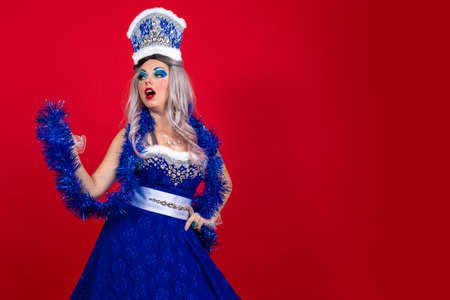 Snow Maiden in an elegant bright blue suit with a crown on her head and a garland in her hands posing on a red background