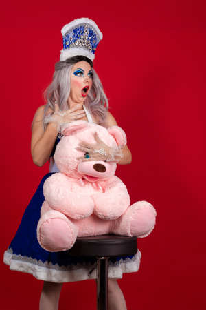 Emotional Snow Maiden in an elegant bright blue suit with a crown posing with a big teddy bear on a red background