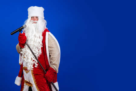 Emotional Santa Claus with a long white beard in a red coat and white hat sings and speaks into a microphone on a stand and poses on a blue background