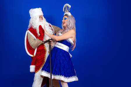 Duet emotional Santa Claus in a red coat and Snow Maiden in a blue suit with a microphone sing on a red background