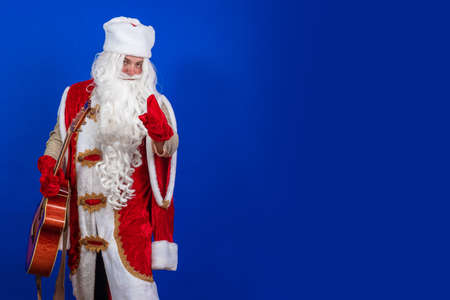 Emotional Santa Claus with a long white beard in a red coat and white hat sings and plays the guitar on a blue background