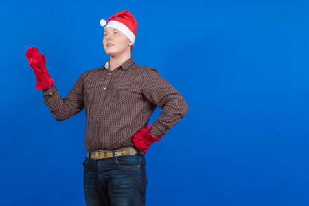 Young guy in a red cap and mittens Santa Claus poses on a blue background