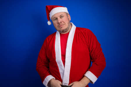 Male actor in costume and hat of Santa Claus posing on a blue background. Stock Photo