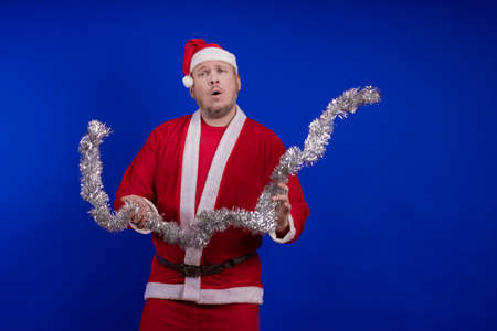 Male actor in a suit and hat of Santa Claus with a silver tinsel garland dancing and posing on a blue background 写真素材