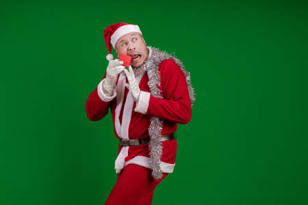 Emotional male actor in a costume of Santa Claus holds a small red gift box in his hands and poses on a green chrome background