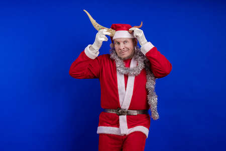 Male actor in a costume of Santa Claus holds horns, jokes, grimaces and poses on a blue background