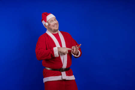 Male actor in costume and hat of Santa Claus posing on a blue background. 写真素材