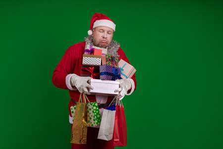 Emotional male actor in a costume of Santa Claus holds a lot of gift boxes and packages in his hands and poses on a green chroma background