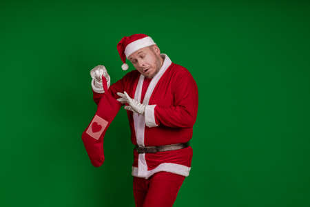 Emotional male actor in a costume of Santa Claus holds a Christmas sock for gifts in his hands and poses on a green chrome background Stock Photo
