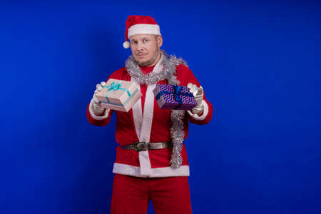 Emotional male actor in a costume of Santa Claus holds gift boxes in his hands and poses on a blue background Stock Photo