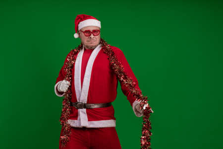 Male actor in a costume of Santa Claus in large pink glasses and with a red garland of tinsel in his hands dancing and posing on a green chrome background 写真素材
