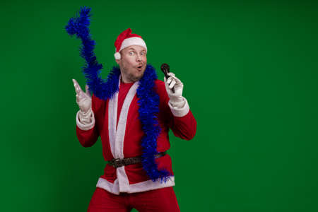 Emotional male actor in a costume of Santa Claus and a blue garland of tinsel holds a microphone in his hands, sings and gestures on a green chrome background