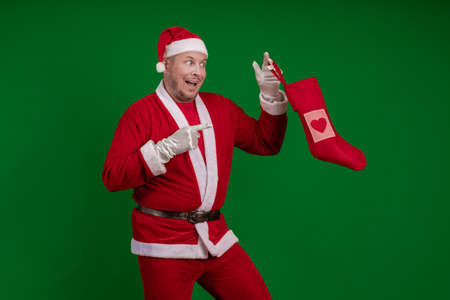 Emotional male actor in a costume of Santa Claus holds a Christmas sock for gifts in his hands and poses on a green chrome background 写真素材