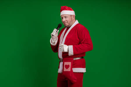 Male actor in a costume of Santa Claus holds a microphone in his hands, sings and poses on a green background
