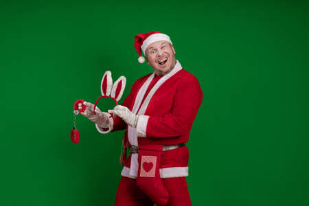 Santa Claus holds red fur handcuffs and a whip in his hands and poses on a green chrome background