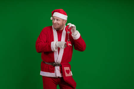 Male actor in a costume of Santa Claus holds red fur handcuffs and a whip in his hands and poses on a green chrome background