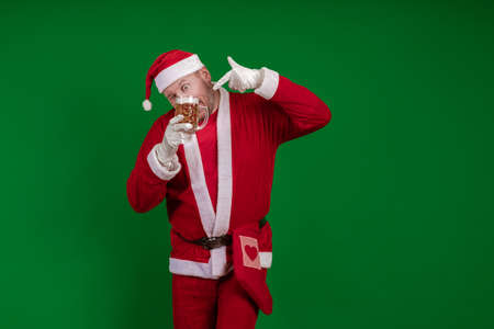 Emotional male actor in a costume of Santa Claus holds a glass of beer in his hands and poses on a green chrome background