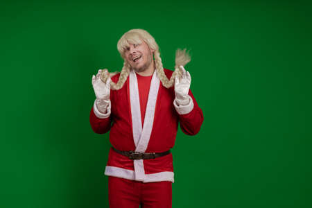 Emotional Santa Claus with long braid hairstyle grimaces and poses on a green chrome background 写真素材