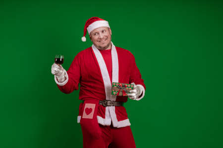 Santa Claus holds one gift box and a glass of wine in his hands and poses on a green chrome background