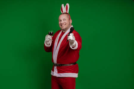 Emotional male actor in a costume of Santa Claus holds a glass of wine in his hands and says a toast to the microphone and poses on a green chrome background Banco de Imagens