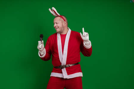 Emotional male actor in a costume of Santa Claus sings and speaks into a microphone and poses on a green chrome background