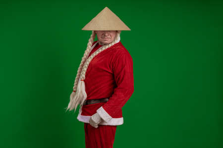 Male actor dressed as Santa Claus with long braids hairstyle and Asian hat posing on green chrome background Banco de Imagens
