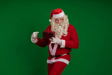 Emotional male actor in a costume of Santa Claus holds one gift box in his hands and poses on a green background