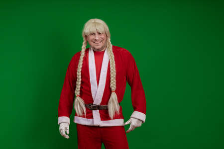 Emotional Santa Claus with long braid hairstyle grimaces and poses on a green chrome background Banco de Imagens