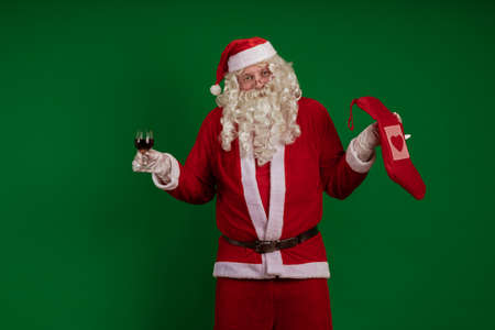 Emotional male actor in a costume of Santa Claus holds one gift box and a glass of wine in his hands and poses on a green chroma background