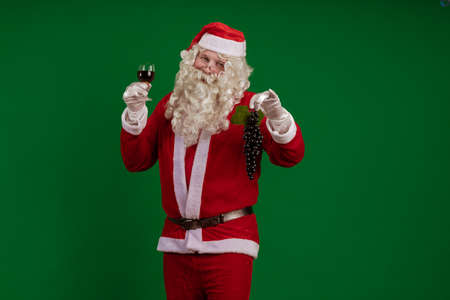 Emotional male actor in a suit of Santa Claus holds a bunch of black grapes and a glass of wine in his hands and poses on a green chroma background