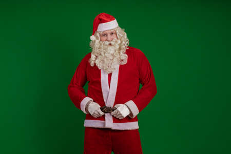 Emotional male actor in a costume of Santa Claus with a long beard gestures and poses on a green chrome background