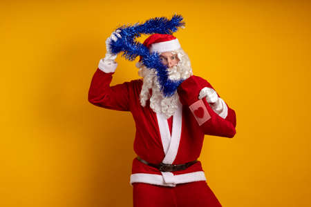 Emotional male actor in a costume of Santa Claus holds in his hands a Christmas sock with gifts and a blue garland of tinsel and poses on a yellow background Banco de Imagens