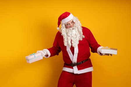 Male actor in a costume of Santa Claus holds two gift boxes in his hands and poses on a yellow background Banco de Imagens