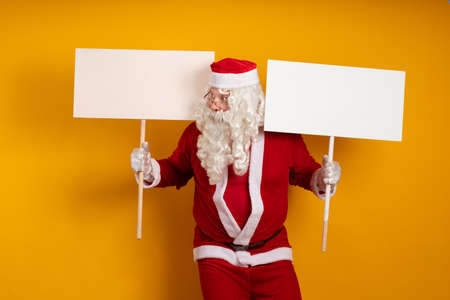 Emotional male actor in a costume of Santa Claus holds in his hands two large white billboards on a stick for recording ads and posing on a yellow background