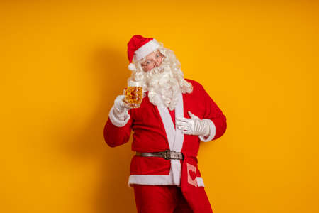 Male actor in a costume of Santa Claus holds in his hands a glass with a light beer and poses on a yellow background