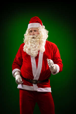 Emotional male actor in a costume of Santa Claus with a long beard gestures and poses on a green background