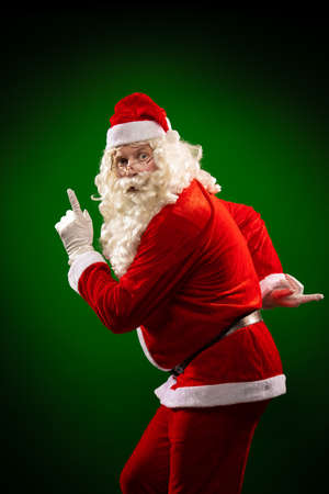 Male actor in a costume of Santa Claus dancing, gesturing and posing
