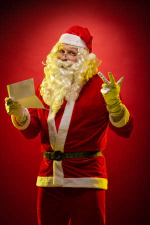 Santa Claus holds a sheet of paper in his hands a Christmas letter reads and poses on a dark red background