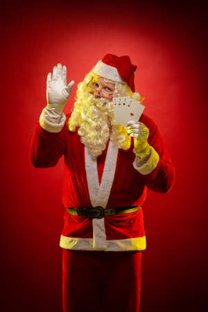 Santa Claus holds playing cards in his hands and poses on a dark red background