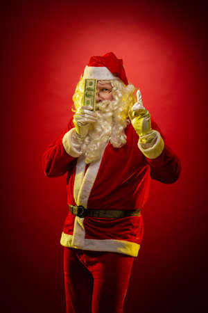 Male actor in a costume of Santa Claus holds in his hands banknotes money and posing on a dark red background