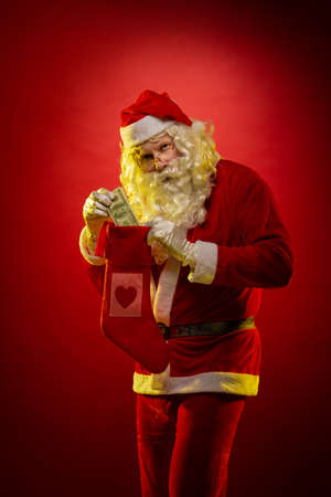 Male actor in a suit of Santa Claus holds in his hands banknotes, money and a Christmas gift sock and poses on a dark red background