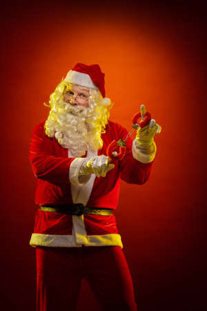 Male actor in a costume of Santa Claus holds red fur handcuffs and a whip in his hands and poses on a dark red background