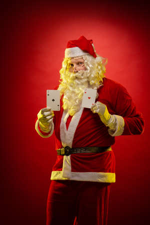 Male actor in a costume of Santa Claus holds playing cards in his hands and poses on a dark red background
