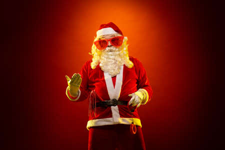 Male actor in a costume of Santa Claus in large pink glasses holds red fur handcuffs and a whip in his hands and poses on a dark red background