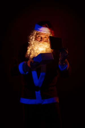Male actor dressed as Santa Claus holds a gift box in his hands, looks into it and poses on a yellow background
