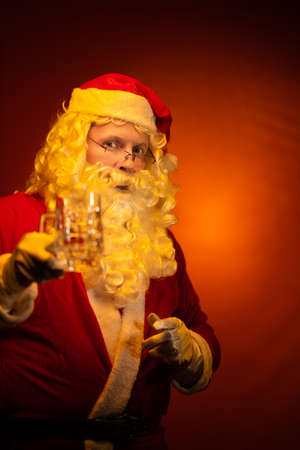 Male actor in a costume of Santa Claus holds a glass of beer and drinks in his hands and poses on a yellow background