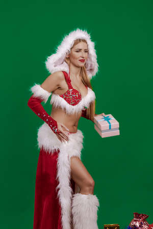 Young girl santa claus with long hair with christmas boxes and gift bags posing on green chroma background